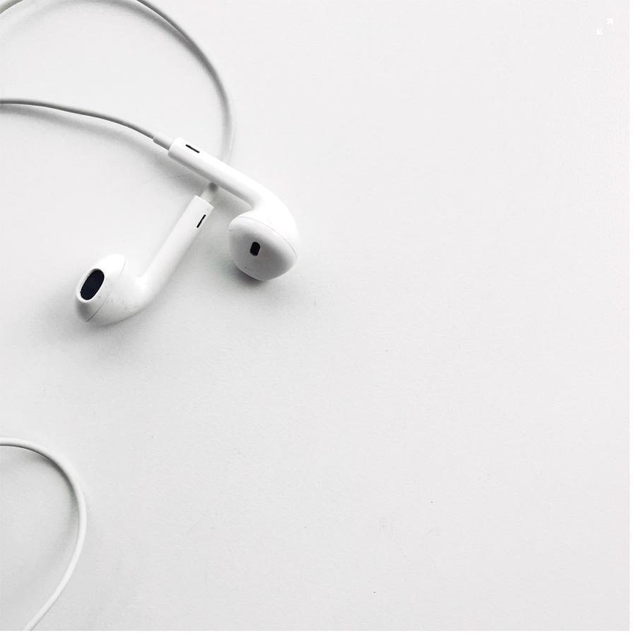 A pair of white earphones with noise cancelling technology.